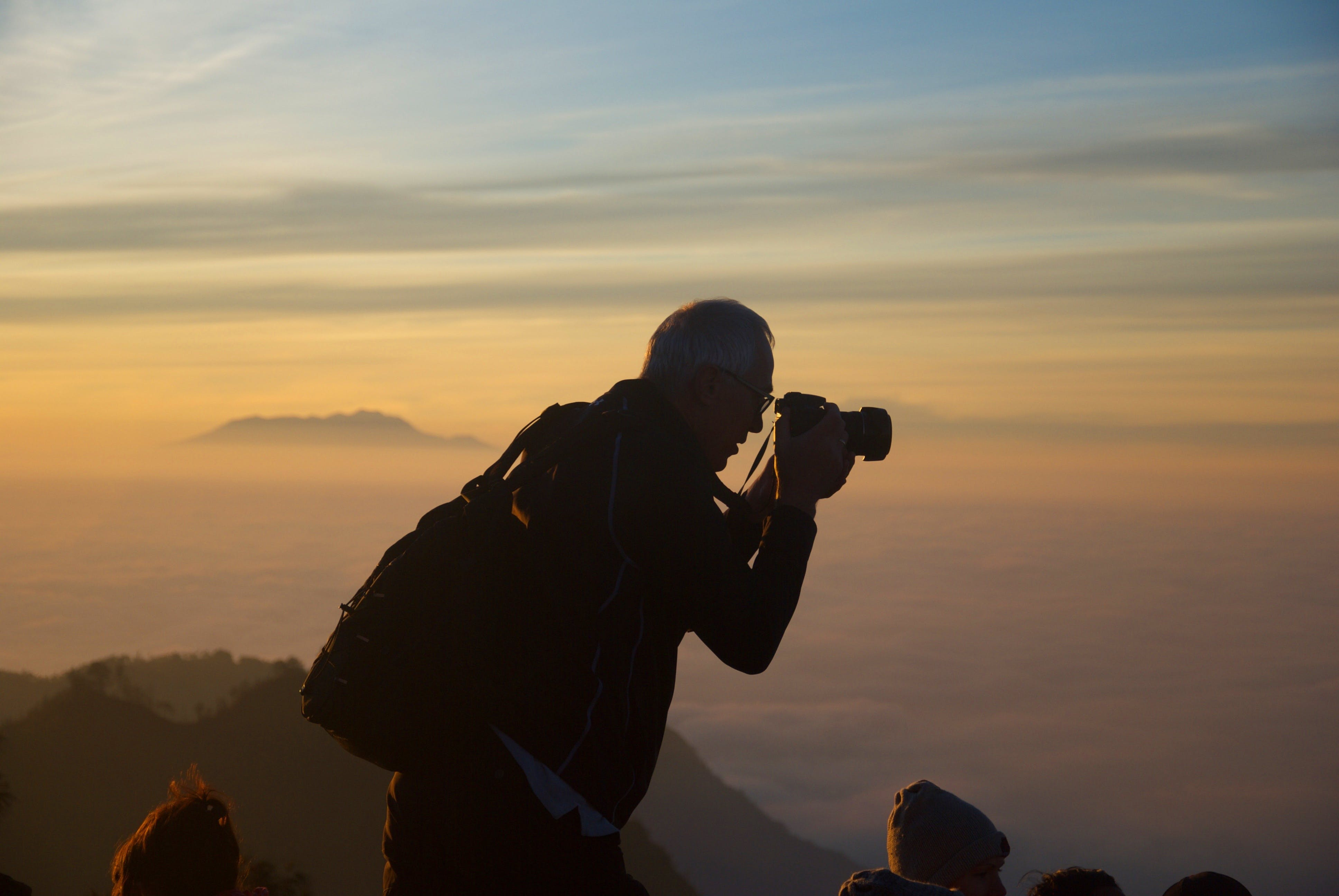 Woman on Mountain Capturing Sea Ocean Under Blue and White Sky during Sunrise