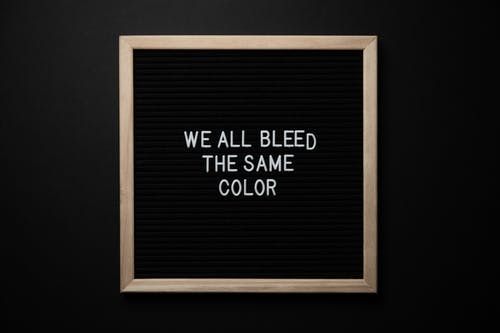 Top view of black signboard with phrase We All Bleed Same Color on surface on black background