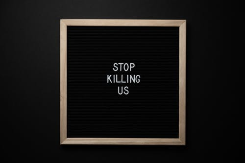 Phrase Stop Killing Us on signboard