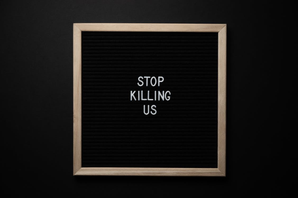 Top view of slogan Stop Killing Us on surface of square blackboard on black background