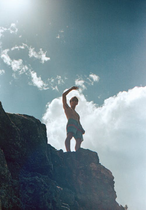 Man in Red Shorts Jumping on Rocky Mountain Under Blue and White Sunny Cloudy Sky during