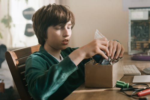 Boy in Green Sweater Holding Silver Iphone 6