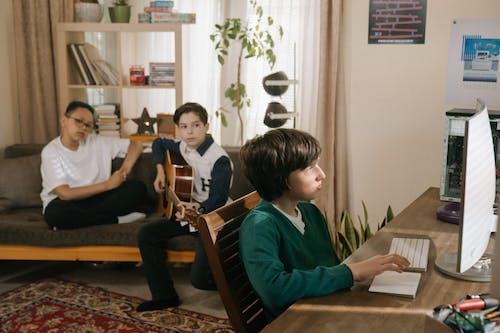 Boy in Blue Long Sleeve Shirt Playing Guitar