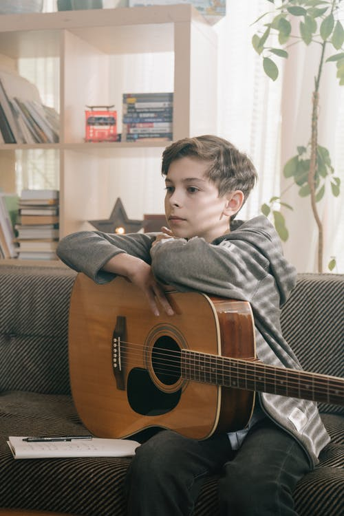 Boy in Gray and Black Stripe Long Sleeve Shirt Playing Brown Acoustic Guitar