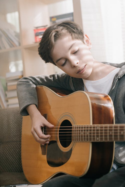 Boy in Gray and Black Crew Neck Shirt Holding Brown Acoustic Guitar
