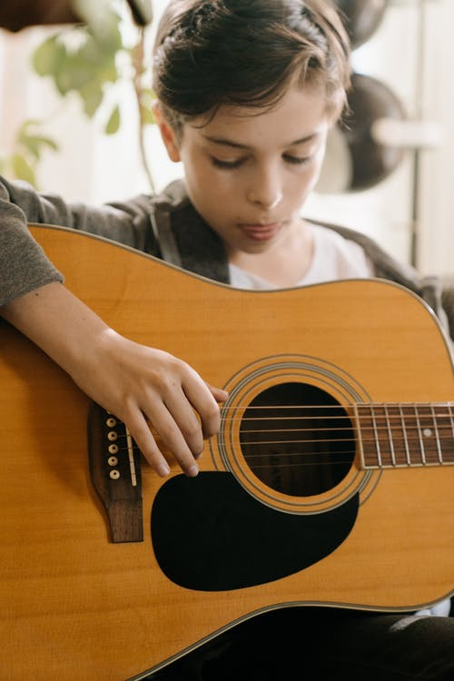 Boy in Gray Long Sleeve Shirt Playing Brown Acoustic Guitar