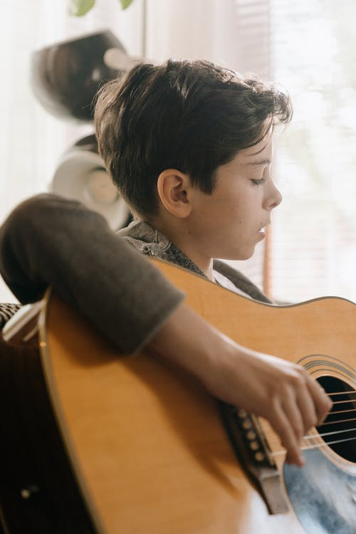Boy in Black T-shirt Playing Brown Acoustic Guitar