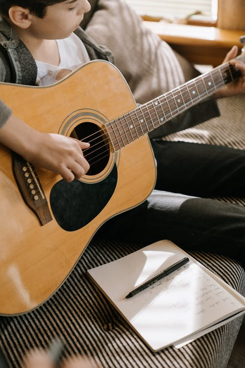 Person Holding Brown Acoustic Guitar