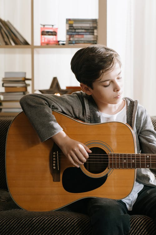 Boy in Gray Sweater Playing Brown Acoustic Guitar