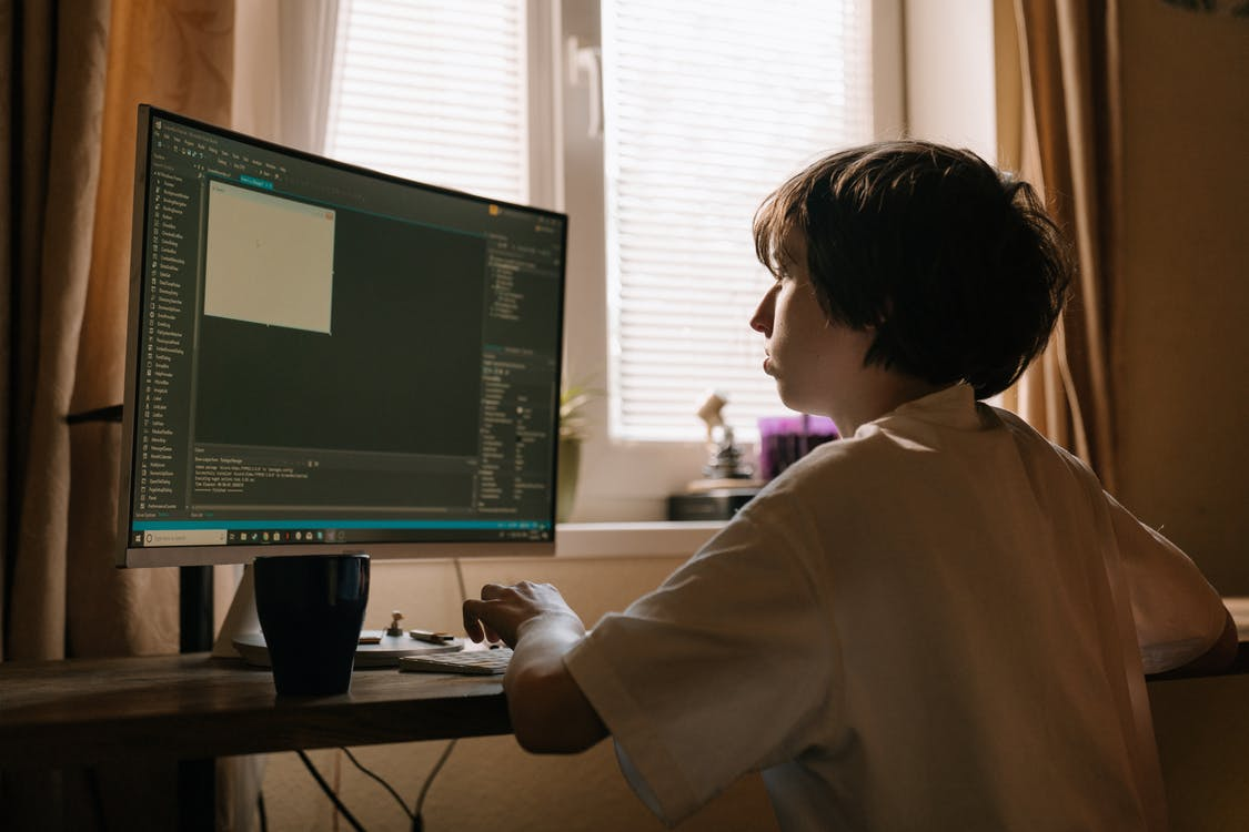 Boy in White Long Sleeve Shirt Playing Computer Game