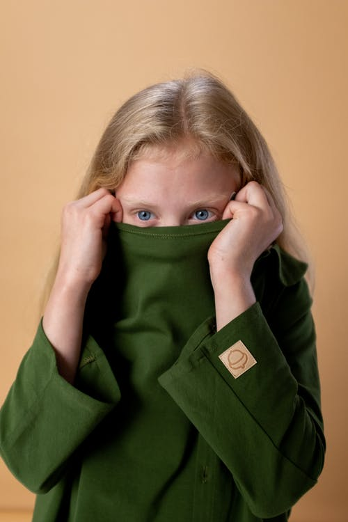 Woman in Green Button Up Long Sleeve Shirt Covering Her Face With Green Textile