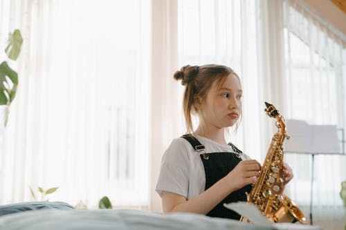 Girl in Black and White Crew Neck T-shirt Playing Saxophone