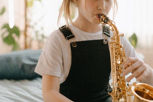 Woman in White Shirt Playing Saxophone
