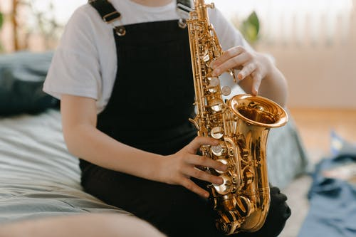Person in Black Sleeveless Dress Holding Saxophone