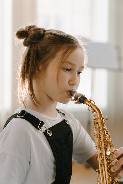 Woman in Black and White Shirt Playing Saxophone