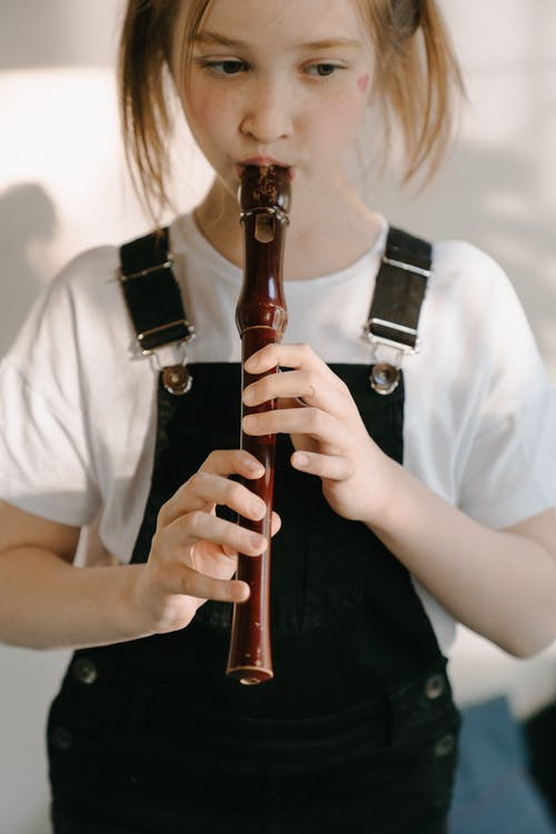 Woman in White Shirt Holding Flute