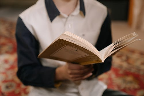 Woman in White Dress Shirt Holding Book
