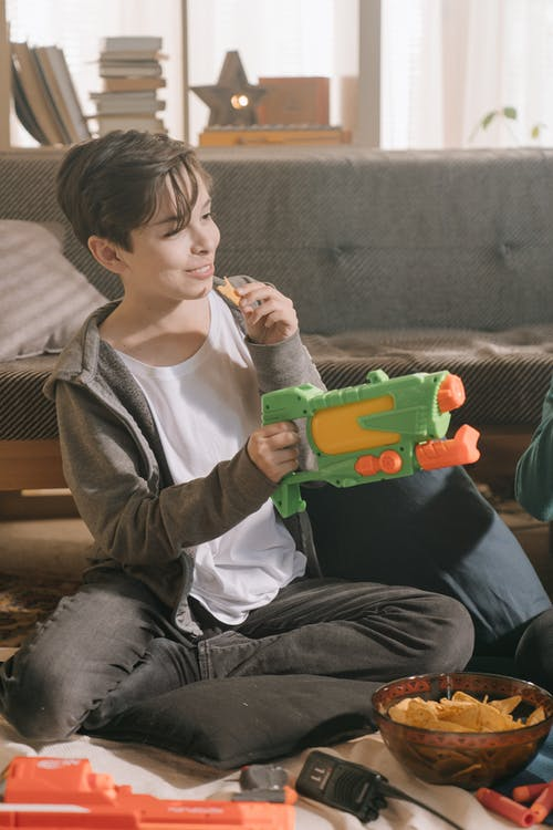 Boy in White Crew Neck Shirt and Gray Jacket Playing Green Toy Car