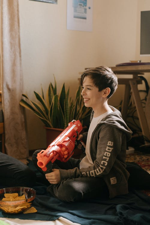 Boy in Black and Gray Jacket Holding Red Plastic Toy Gun