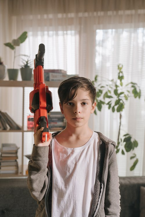 Girl in White Crew Neck Shirt Holding Red and Black Toy Gun