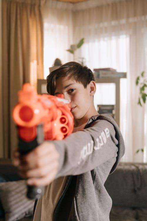 Boy in Gray Hoodie Holding Red Toy Gun