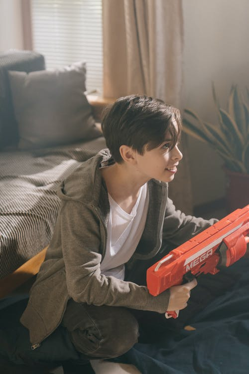 Boy in Gray Hoodie Playing Red Toy Gun