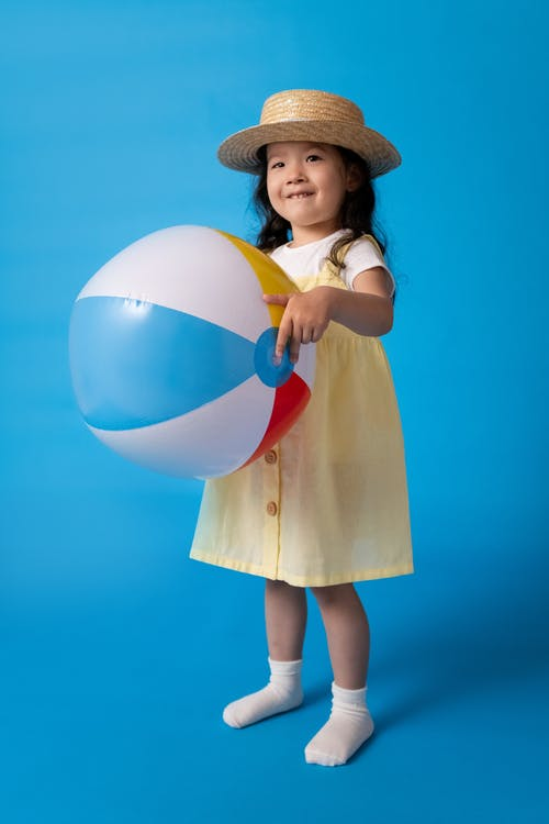 Girl in Brown Dress Holding White Blue and Yellow Inflatable Ball
