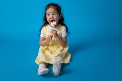 Girl in Yellow Dress Holding White and Pink Pacifier