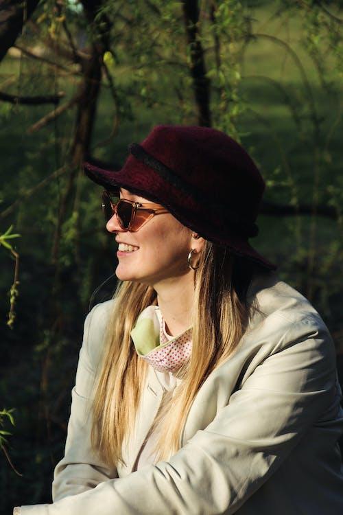 Woman in White Coat Wearing Maroon Hat
