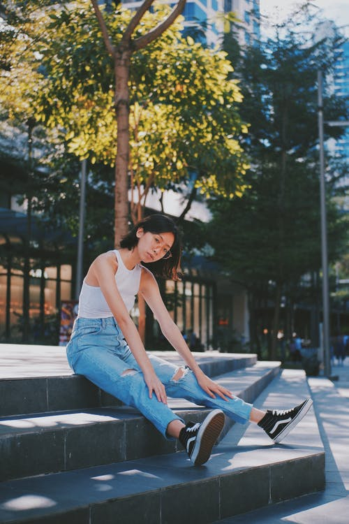 Woman in White Top and Blue Denim Jeans Sitting on Stairs