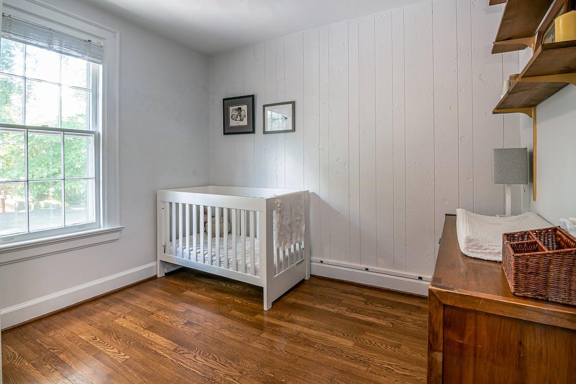 White Wooden Crib Beside White Wall
