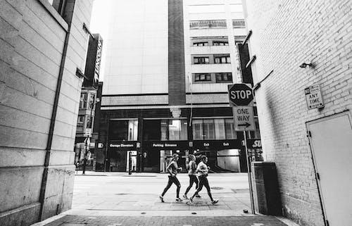 Grayscale Photo of People Walking on Sidewalk Near Builidngs