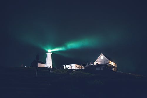 Green lighthouse in dark night on hill