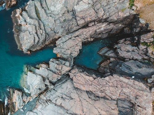 Rough rocks between blue sea water in daylight