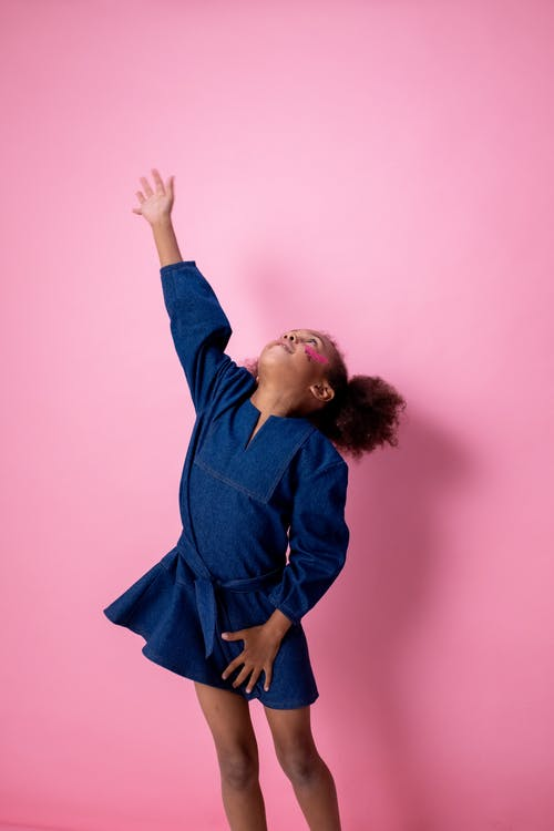 Woman in Blue Long Sleeve Shirt Raising Her Right Hand