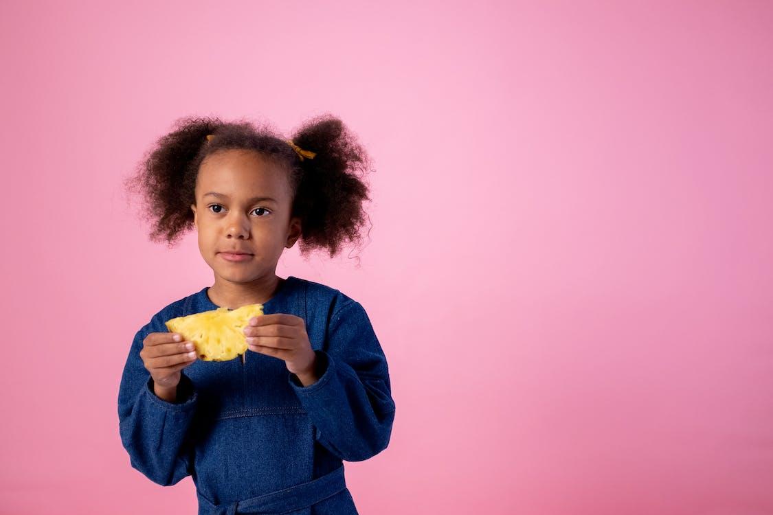 Girl in Blue Long Sleeve Shirt Holding Yellow Flower