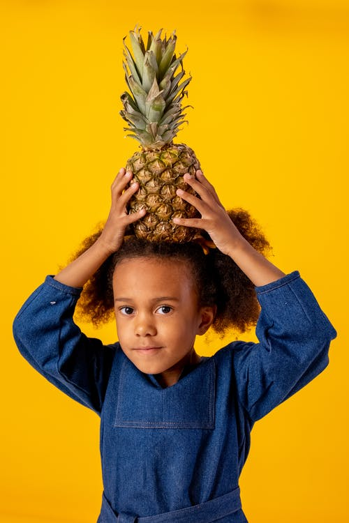 Boy in Blue Collared Shirt Holding Pineapple