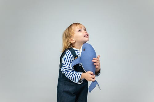Girl in Blue and White Striped Long Sleeve Shirt Holding Blue Balloon