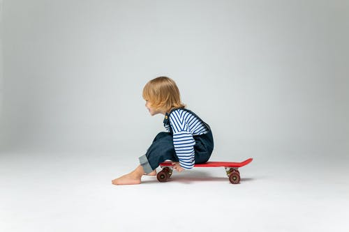 Boy in Black and White Striped Long Sleeve Shirt Sitting on Red Skateboard