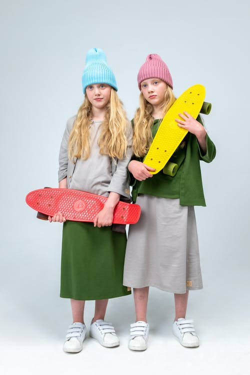 2 Women Holding Yellow and Pink Surfboard