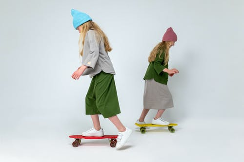 2 Women in Green Dress Standing on Red and White Skateboard
