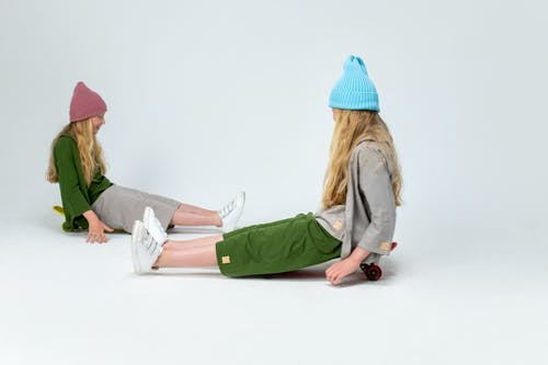 Woman in Green Jacket and Blue Knit Cap Sitting on White Floor