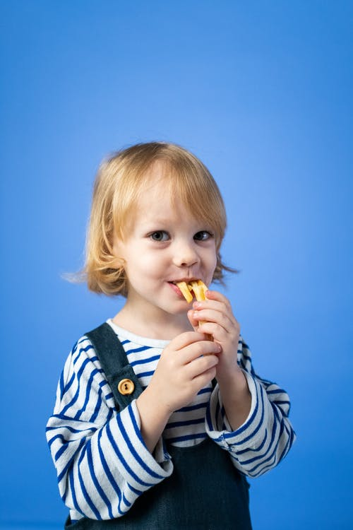 Girl in Black and White Stripe Long Sleeve Shirt Eating Yellow Food