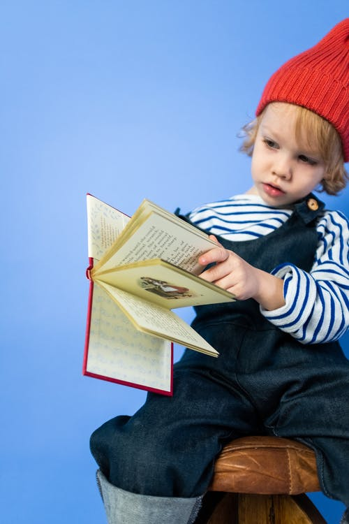 Boy in Black and White Striped Long Sleeve Shirt Reading Book