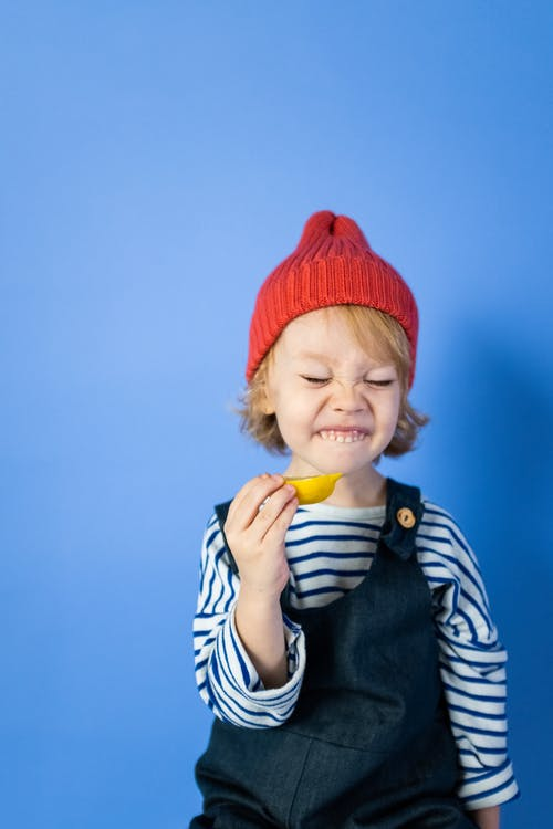 Boy in Red Knit Cap and Black and White Striped Shirt Eating Yellow Fruit