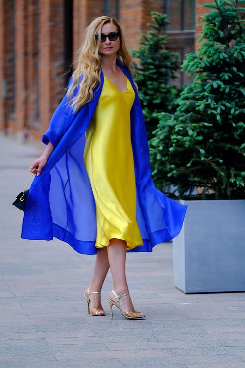 Full body of self esteem young female with long blond hair in trendy yellow dress and blue coat spinning around on city street