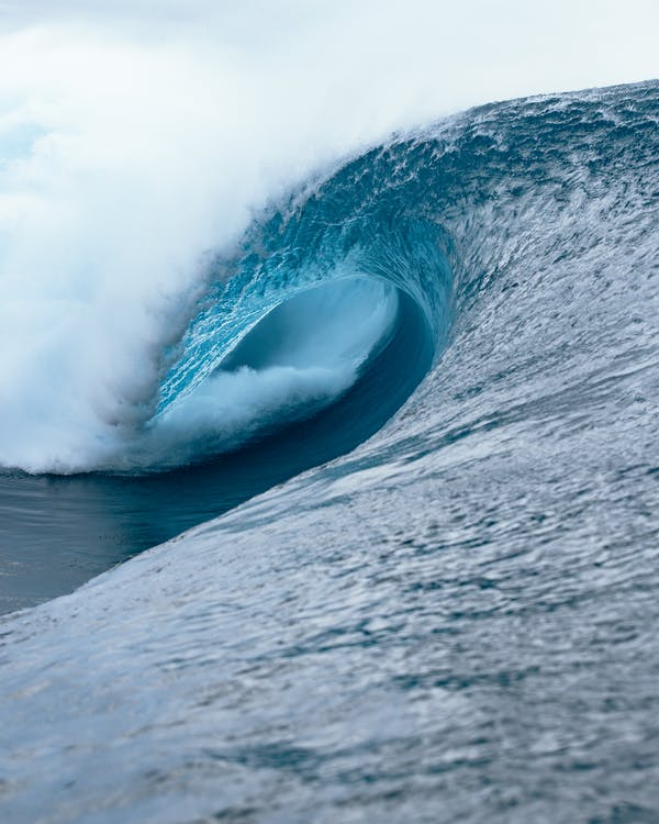 Picturesque view of clear blue crest of wave crashing on surface on surface of water