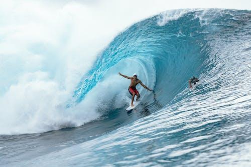 Surfer riding under crest of wave