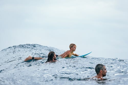 Group of people swimming with surfboard on waves and looking ahead against sky