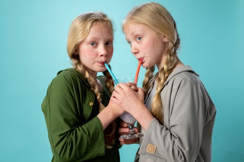 2 Women Drinking from a Cup